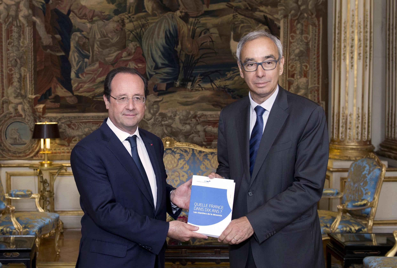 Le président français, François Hollande et l'économiste Jean Pisani-Ferry avec le rapport « La France dans 10 ans », à l'Elysée le 25 juin 2014.