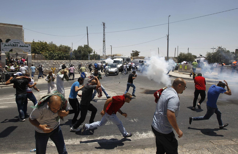 Палестинские протестующие разбегаются от слезоточивого газа, используемого против них израильскими военными, восточный Иерусалим, 4 июля 2014 г.