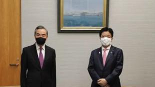 中国外长王毅与日本内阁官房长官加藤胜信资料图片