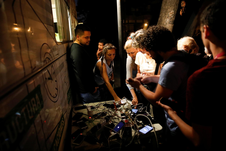 População carrega celulares em geradores públicos durante apagão na Venezuela.