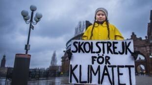 """A sueca Greta Thunberg durante manifestação diante do parlamento em Estocolmo (30/11/18). Na faixa, lê-se: """"Greve da escola pelo clima""""."""