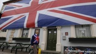 """Человек, одетый в британский флаг, перед пабом """"Герцог Йоркский"""" в Стокпорте на севере Англии, украшенным британским флагом по случаю """"бриллиантового юбилея"""" правления Елизаветы II"""
