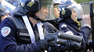 Un policier anti-émeute fait face aux jeunes de banlieue avec son flash-ball, au cours d'une manifestation à Nanterre.