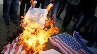 Waandamanaji wa Wapalestina wakichoma moto picha inayoonyesha rais wa Marekani Donald Trump na bendera ya Marekani wakati wa maandamano dhidi ya uamuzi wa Trump kutambua Jerusalem kama mji mkuu wa Israel katika mji wa Gaza tarehe 7 Desemba 2017.