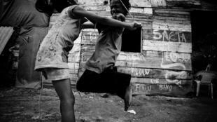 En Cartagena, el líder comunitario Eliécer Barón organizó una escuela para los hijos de los desplazados. Dos niños juegan frente a su casa.