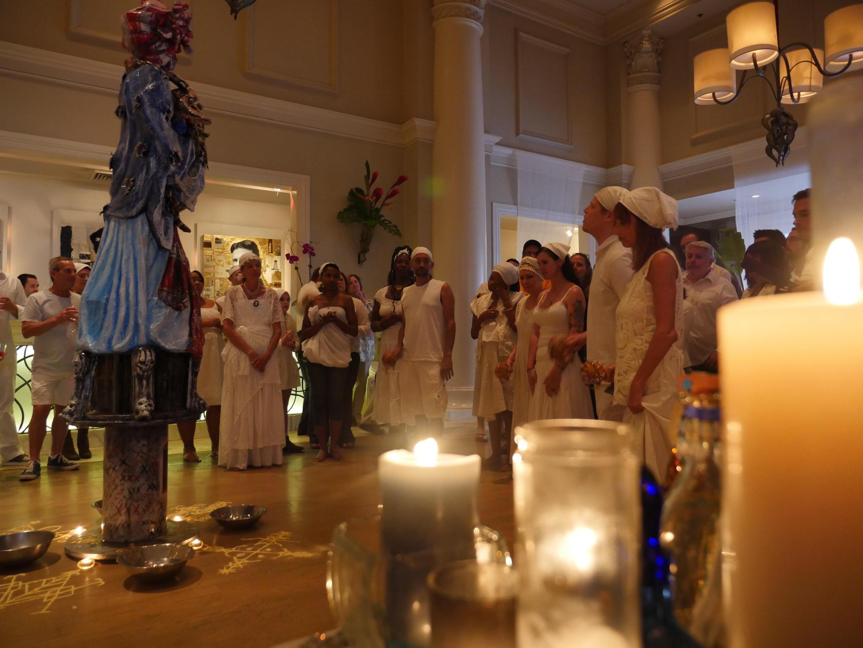 Des pratiquants du vaudou habillés tout en blanc réunis devant une statue de la prêtresse vaudou Marie Laveau, ainsi que devant un autel dédié aux « loas », les esprits vaudou.