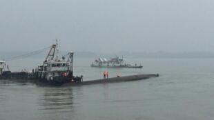 Спасатели слышат стук, доносящийся из перевернутого корабля, часть которого видна над водой.