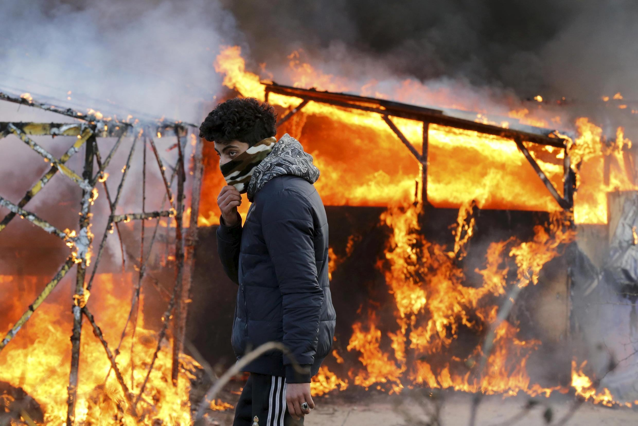 """A migrant walks past a burning makeshift shelter set ablaze in protest against the partial dismantlement of the camp for migrants called the """"jungle"""", in Calais"""