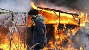 "A migrant walks past a burning makeshift shelter set ablaze in protest against the partial dismantlement of the camp for migrants called the ""jungle"", in Calais"