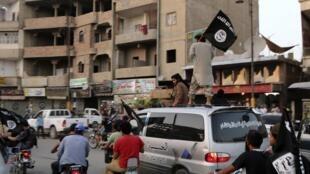 Des membres du groupe EI brandissent le drapeau noir du jihad aux alentours de Raqqa le 29 juin 2014.