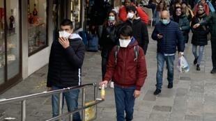 Mazauna Milan a Italiya da suka fita waje da mayanin Milan fuska don kada su kamu da cutar coronavirus.