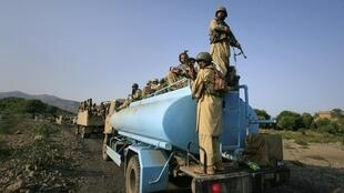 Soldiers sit atop of a water tanker while travelling on a road in Tora Warai, a town in Kurram Agency