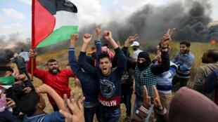 Les Palestiniens crient lors des affrontements avec les troupes israéliennes le long de la frontière entre Israël et Gaza, demandant le droit de retourner dans leur patrie, au sud de la bande de Gaza, le 30 mars 2018.