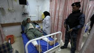 Bagdad, 19 février 2012. Un policier blessé lors de l'attentat suicide, veillé par l'un de ses camarades.