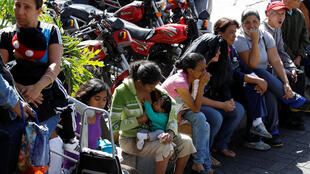 Venezuelanos aguardam abertura de supermercado em Caracas, neste sábado (6).