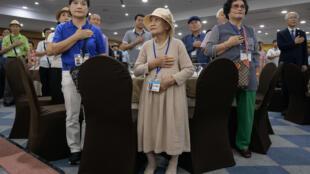 Les participants sud-coréens des réunions familiales inter-coréennes se présentent pour l'hymne national alors qu'ils se réunissent à la veille du départ pour la Corée du Nord, dans un hôtel de Sokcho, le 19 août 2018.