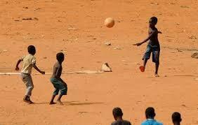 Meninos brincando em terreno árido, em Angola