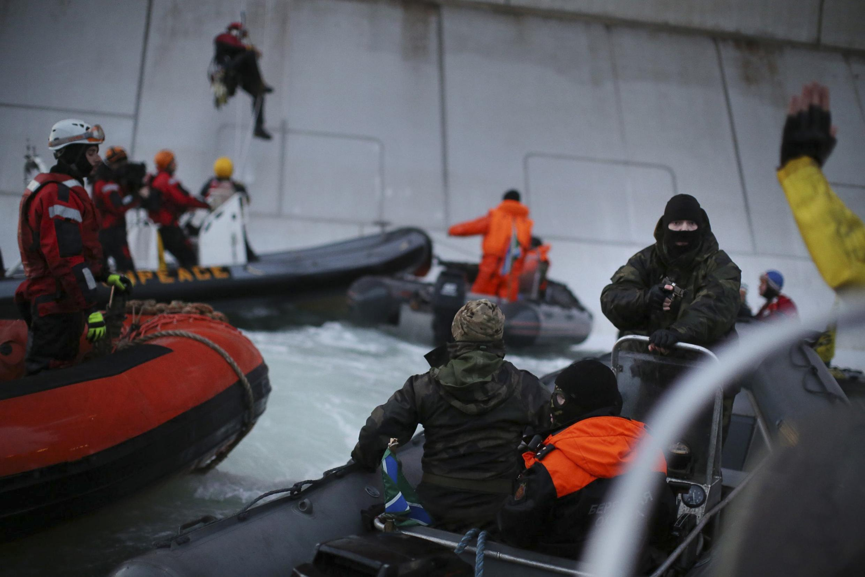 Theo Greenpeace, một người bịt mặt - được nhận dạng là một lính Tuần duyên Nga (P) - đã chĩa súng vào các thành viên Greenpeace nhân vụ phản đối gần giàn khoan của Gazprom tại biển Pechora ngày 18/09/2013.