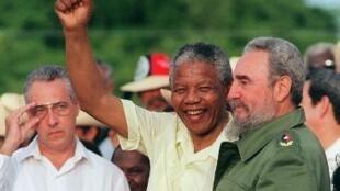 «Madiba» poing levé aux côtés de Fidel Castro (d), salue les Cubains, le 26 juillet 1991, à Matanzas.