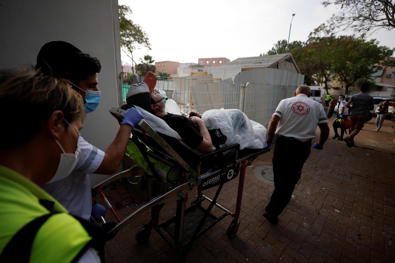 Médicos israelíes evacuan a un hombre herido después de que un cohete lanzado desde la Franja de Gaza impactara en un edificio residencial en Ashkelon, al sur de Israel el 11 de mayo de 2021. REUTERS/Amir Cohen