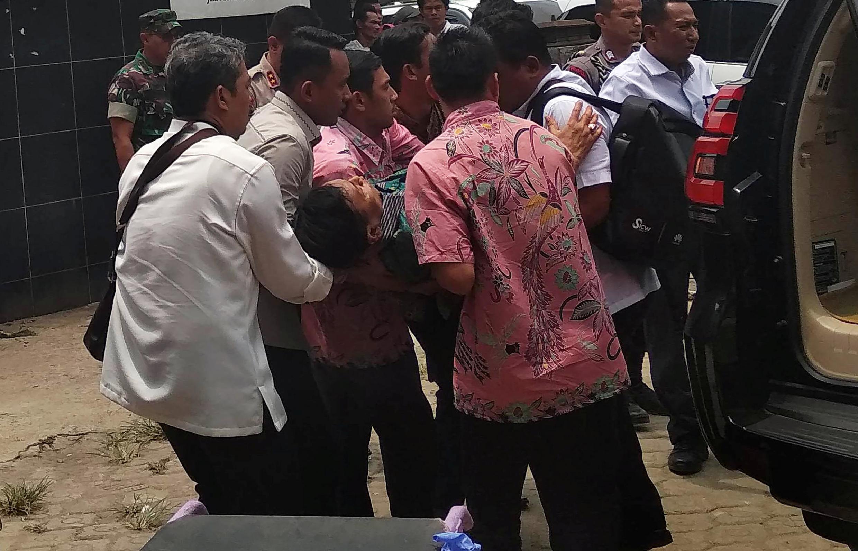 Le ministre indonésien de la Sécurité, Wiranto, est transporté d'une voiture à la salle d'urgence après avoir été agressé à Pandeglang, dans la province de Banten, le 10 octobre 2019.