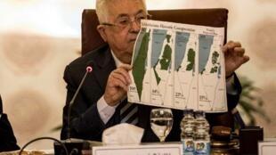 Le président de l'Autorité palestinienne, Mahmoud Abbas, montre des cartes de la Palestine où l'on voit le plan de partition de l'ONU de 1947, les frontières de 1948-67 et une carte sans les zones annexées par Israël, au Caire, le 1er février 2020.