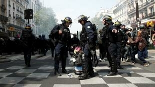 French CRS riot police apprehend a protester during clashes at a demonstration during the traditional May Day march in Paris.