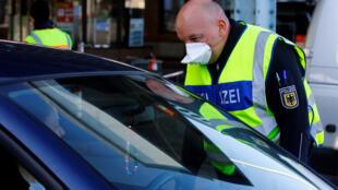 一名德国边警检查与瑞士边境过往车辆。 2020年3月16日照片