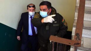 Le ministre de la santé bolivien Marcelo Navajas (à gauche), accompagné du directeur de la Force spéciale de lutte contre la criminalité Ivan Rojas, lors de son arrivée à La Paz le 20 mai 2020.