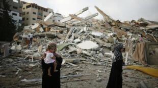 Mulheres palestinas observam escombros de um prédio residencial em Gaza, em 24 de agosto de 2014.