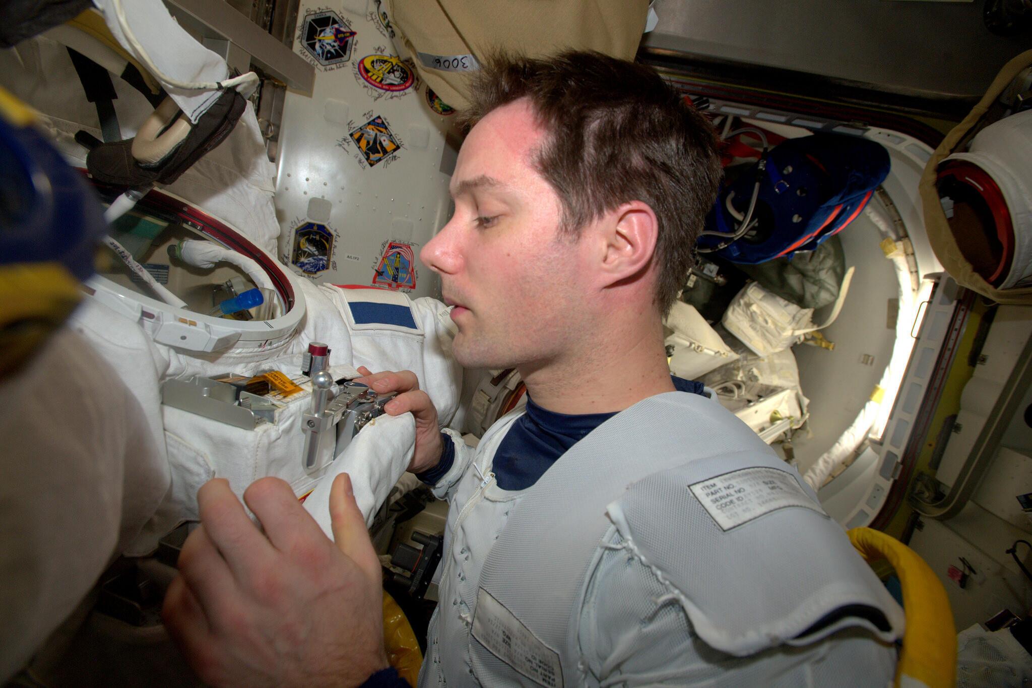 Thomas Pesquet inspecte le module de commande et d'affichage de son scaphandre avant sa sortie dans l'espace.