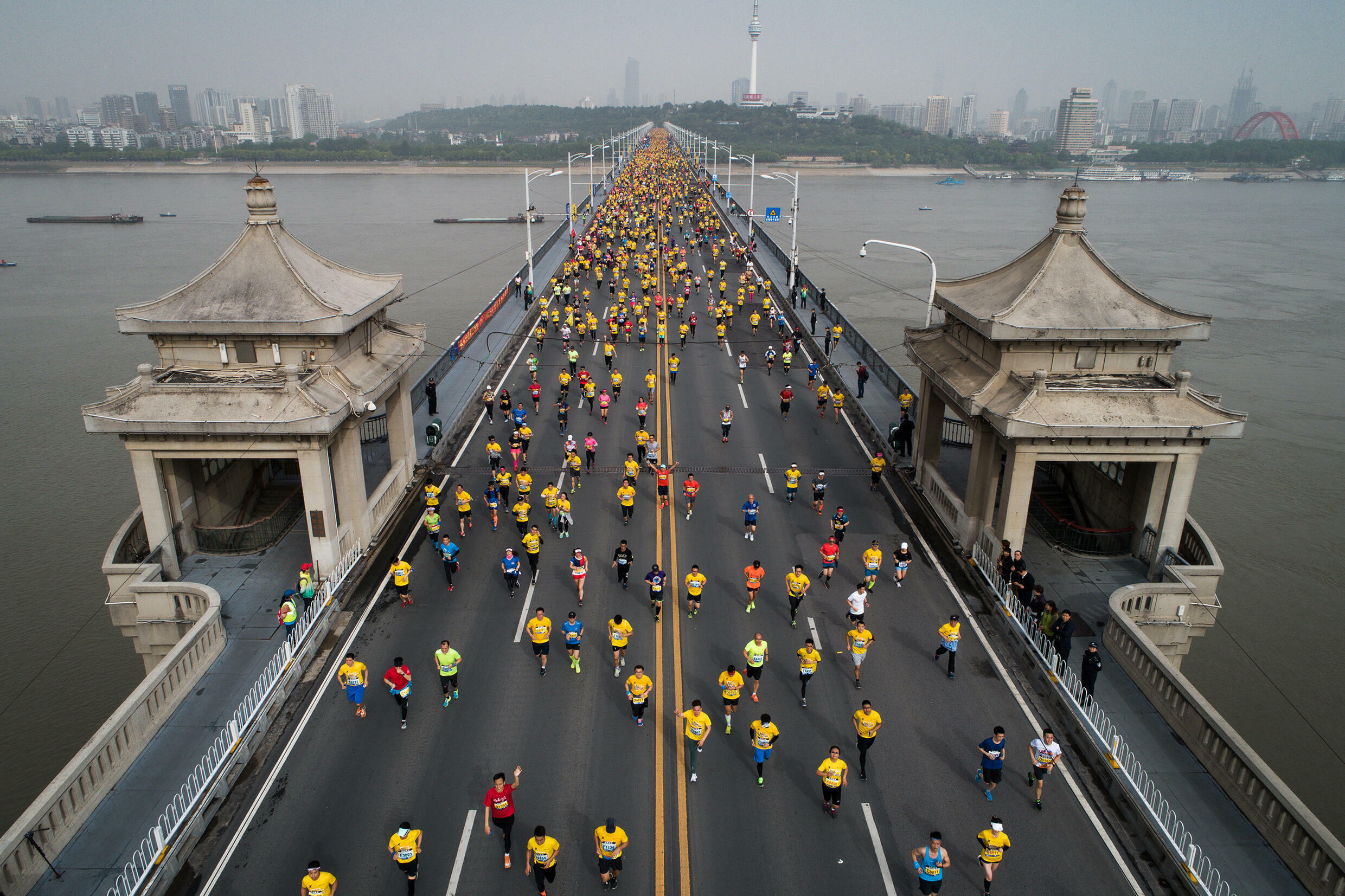 Wuhan marathon runners cross the Yangtze River bridge in 2018. This year's event was postponed at short notice because of Covid fears