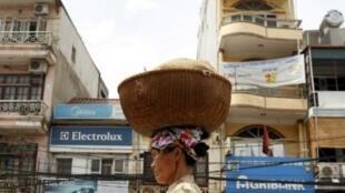 Một phụ nữ nhập cư bán bánh mì rong trên đường phố Hà Nội. Lạm phát gia tăng, cuộc sống người nghèo càng thêm khốn khó. Ảnh chụp ngày 11/5/11.