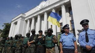 Des volontaires du bataillon Donbass et du groupe d'auto-défense de Maïdan tiennent la garde du Parlement ukrainien à Kiev, le 3 juillet 2014, aux côtés des officiers de sécurité (à droite).