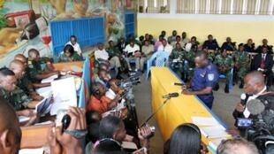L'ancien chef de police à Kinshasa, John Numbi, (2D) écrit sur un morceau de papier aux côtés d'un avocat lors d'une audience au tribunal, le 27 janvier 2011..