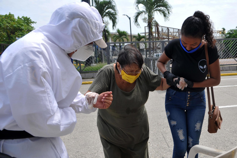 Un infirmier aide une femme atteinte du coronavirus à Guayaquil, en Équateur, le 30 avril 2020.