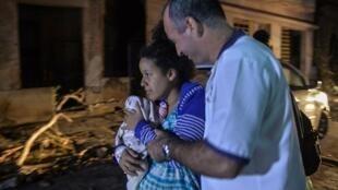 Un paramédico asiste a una mujer evacuada junto a su bebé en el barrio de Luyano de La Habana, el 28 de enero de 2019.