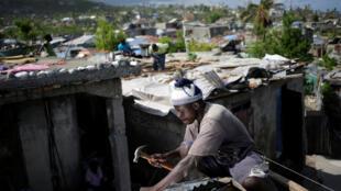À Jérémie, un homme répare le toit d'une maison touchée par l'ouragan Matthew, le 31 octobre 2016.