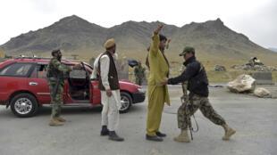 Soldados del Ejército Nacional Afgano (ANA) registran a hombres en un puesto de control en la carretera en las afueras de Kabul, el 29 de abril de 2021.