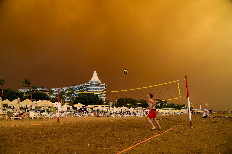 De grands nuages noirs s'approchent de complexes touristiques alors qu'un important incendie ravage le district  de Manavgat, jeudi 29 juillet 2021.