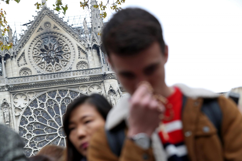 Fieles rezando cerca de Notre-Dame tras el incendio, 16 de abril de 2019. REUTERS/Yves Herman