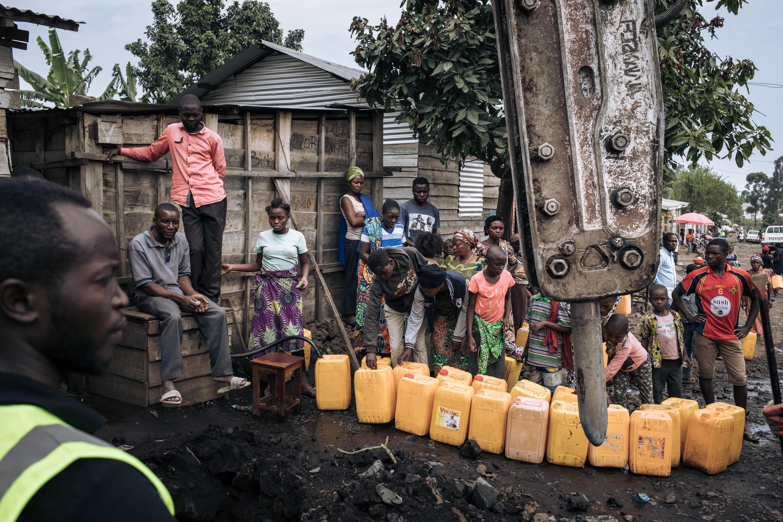 Habitantes de Goma llenan bidones de agua, el 28 de mayo de 2021, mientras obreros arreglan las canalizaciones rotas tras la erupción del volcán Nyiragongo, en República Democrática del Congo