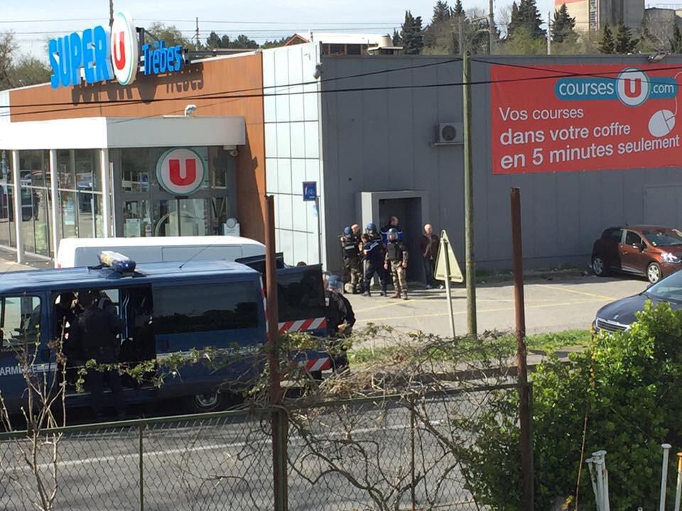 Des forces de polices devant le supermarché de Trèbes, où une prise d'otages est en cours, vendredi 23 mars 2018, dans le sud de la France.