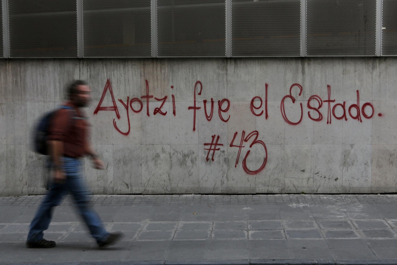 """En México un hombre pasa frente a graffitti en apoyo a los 43 estudiantes desaparecidos """"Ayotzi, fue el Estado"""", el 26 de abril de 2015"""
