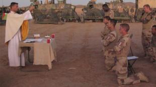 Chaque soir, entre les blindés, le « padre » organise une messe.  Sur 190 soldats, une dizaine assiste chaque soir à l'office.