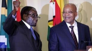 Le président du Zimbabwe Robert Mugabe (g).