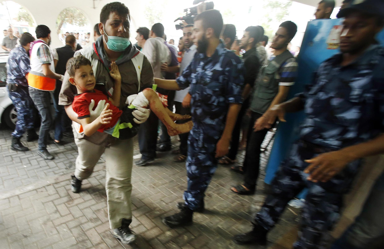 Un Palestinien transporte un enfant blessé dans le bombardement du quartier de Chajaya, à l'hôpital de Gaza-Ville, ce dimanche 20 juillet.