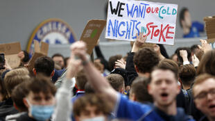 Football supporters hold placards as they demonstrate against the proposed European Super League