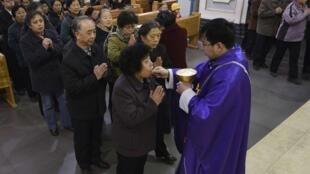 Les catholiques de Taiyuan, dans la province de Shanxi en Chine reçoivent la communion, le lendemain de l'élection du Pape François.