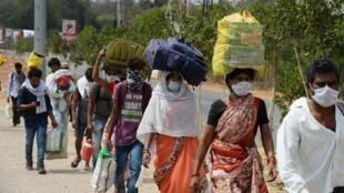 Interdits de travail à cause du confinement, des travailleurs migrants tentent de rejoindre leur village, dans la banlieue de Hyderabad, dans l'État indien du Maharashtra, le 28 avril 2020.